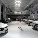 Anna standing amongst her favorite collection of cars